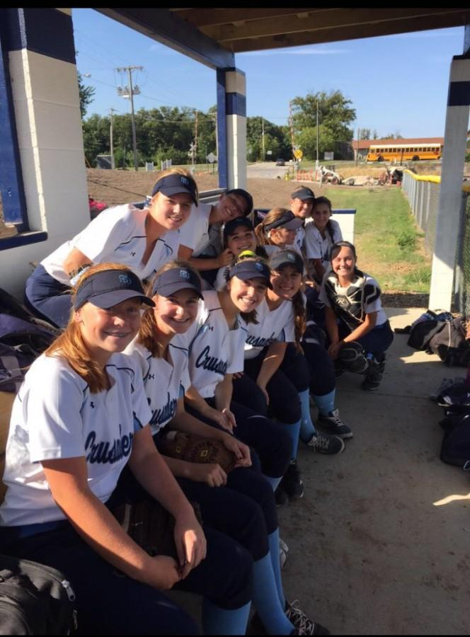 The ladies pose for a picture in the dugout.