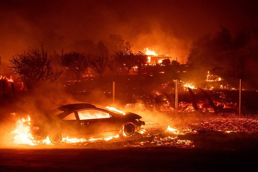 Flames destroy homes and vehicles as the fire tears through Paradise, California on November 8, 2018.