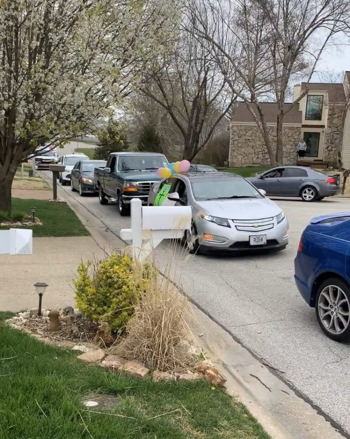 A train of cars filled with friends and family head down the street for a drive-by birthday surprise.