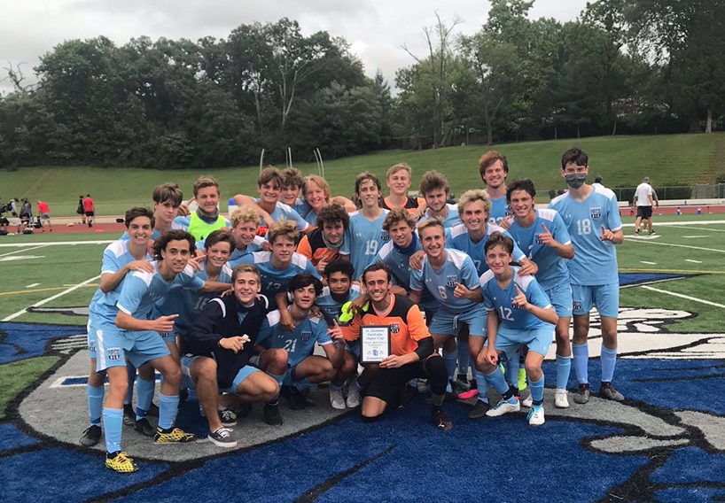 The varsity boys soccer team celebrates after their tournament win