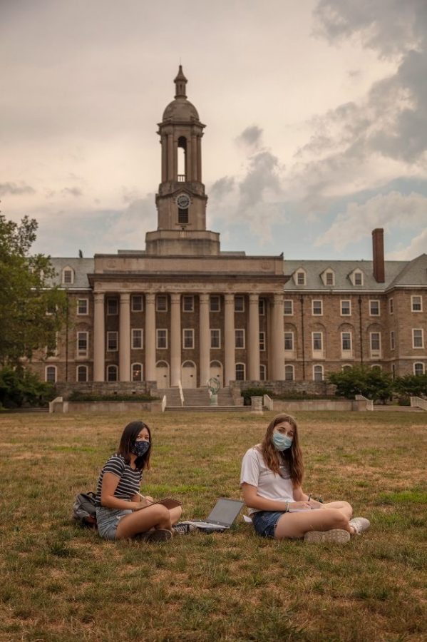 Two college sophomores wear masks as they return to campus