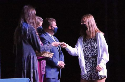 Senior Emily Lieurance receives a pin from Mrs. Stewart and Mr. Welby after being inducted into NHS.