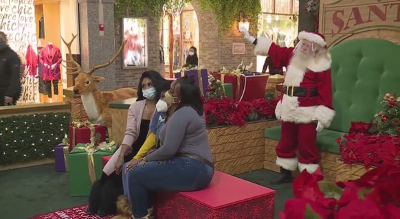 At West County mall, this family snaps a pic with Santa while still wearing masks and staying social distant