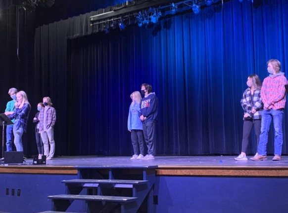The class of 2022 snowcoming court (Alli Herbert and Garrett Havrilla, Zach Fink and Paige Deeken, and Mia Pointer and Grant Richards from right to left) stand on stage for the junior pep rally.