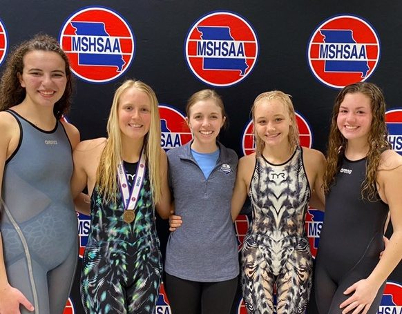 From left to right: Caroline Cunningham, Kallie Nero, Coach Honerkamp, Sydney Pickett, and Elise Newman celebrate the swim teams' success at state.
