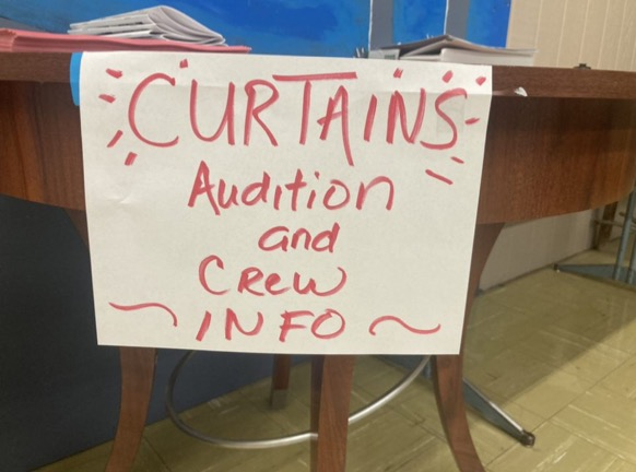 a sign announcing the musical and information is placed on a table outside of Mrs. Findley's room.